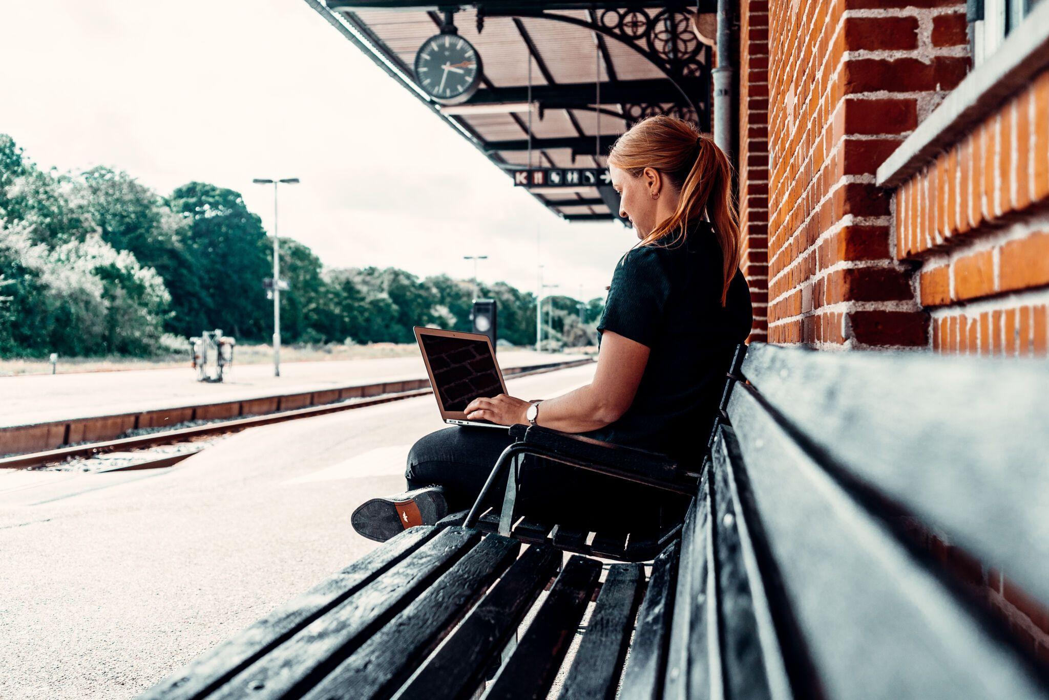 Billede af Dorte Toft siddende på en bænk på Thisted Station