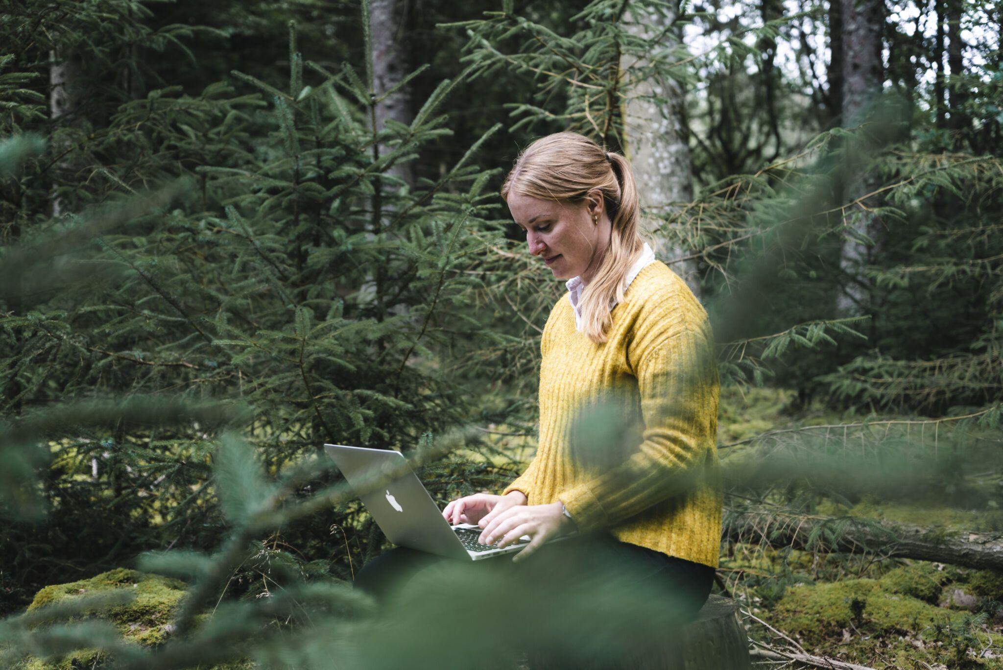Dorte Toft i skoven med computer på skødet