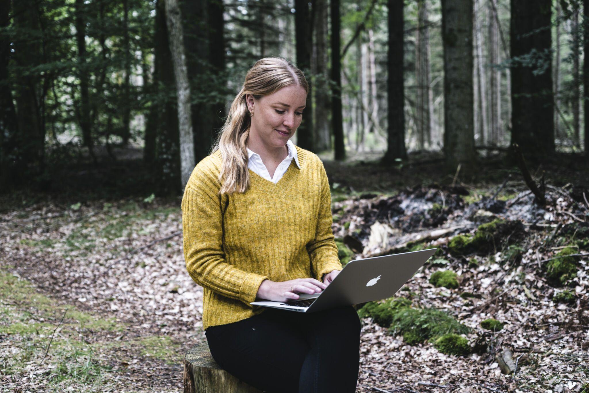 Dorte Toft siddende på træstub med bærbar computer
