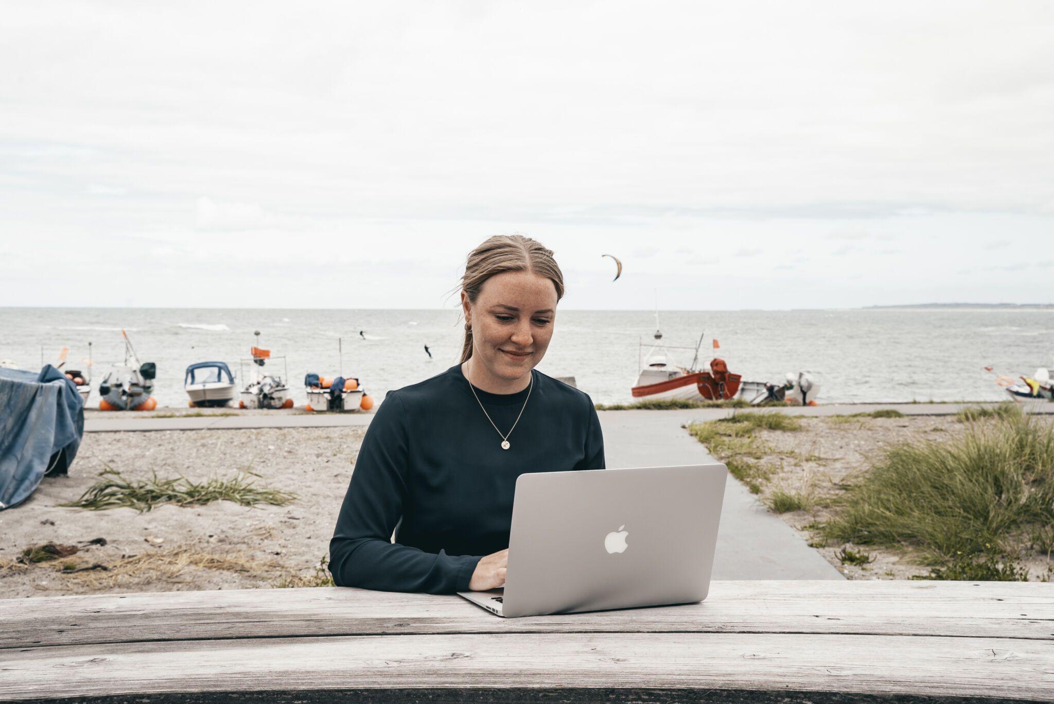 Billede af Dorte Toft på bænk ved havet i baggrunden