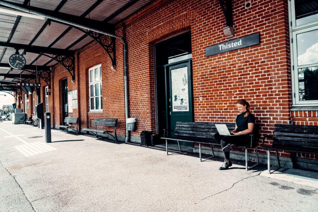 Dorte Toft siddende på en bænk på Thisted Station